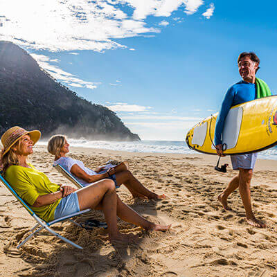 Man with surfboard and women sitting on beach