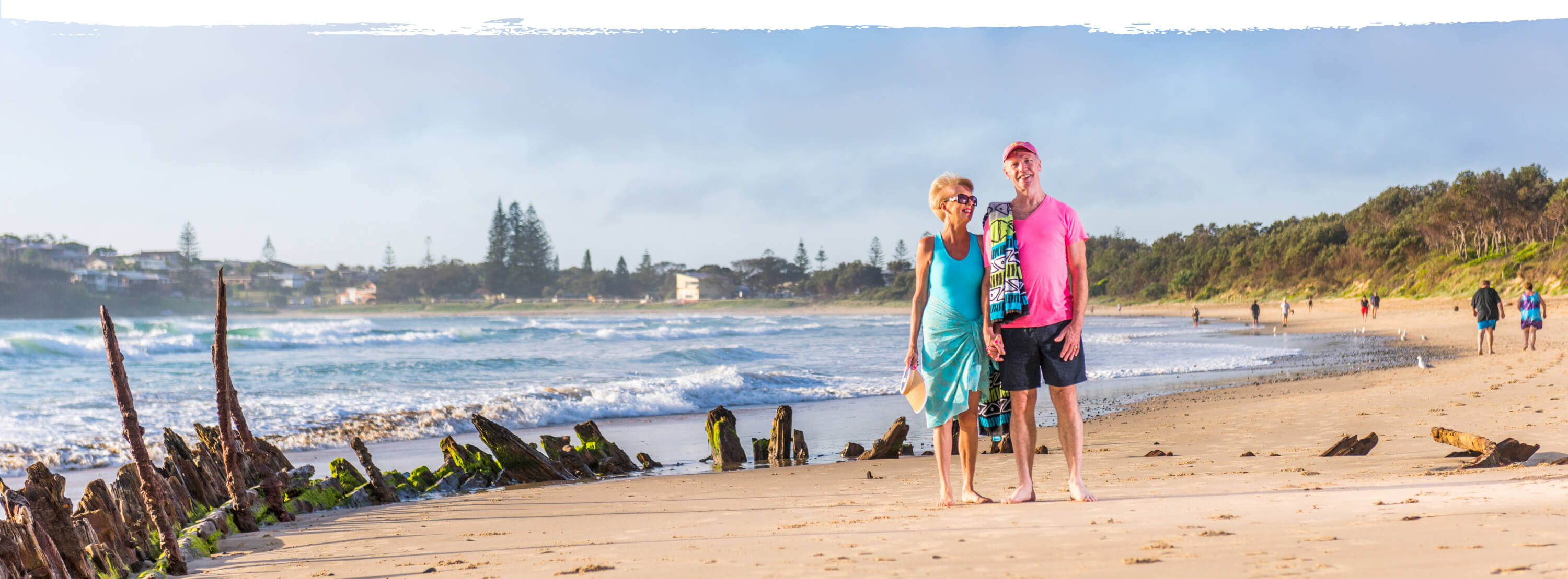over 50s couple wlaking on beach near The Buster shipwreck in Woolgoolga